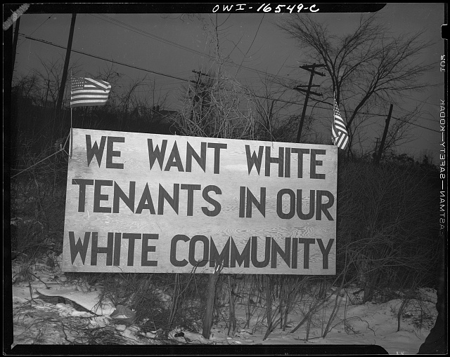 "Detroit, Michigan. Riot at the Sojourner Truth homes, a new U.Sn federal housing project, caused by white neighbors' attempt to prevent Negro tenants from moving in. Sign with American flag ""We want white tenants in our white community,"" directly opposite the housing project"