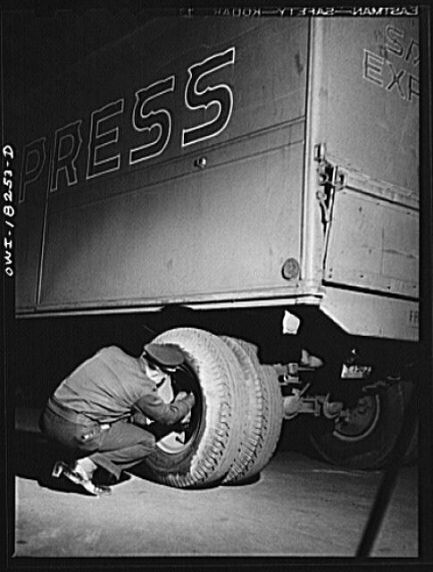 Driver checking tires outside a diner where he has stopped for dinner along U.S. Highway 40 in Delaware