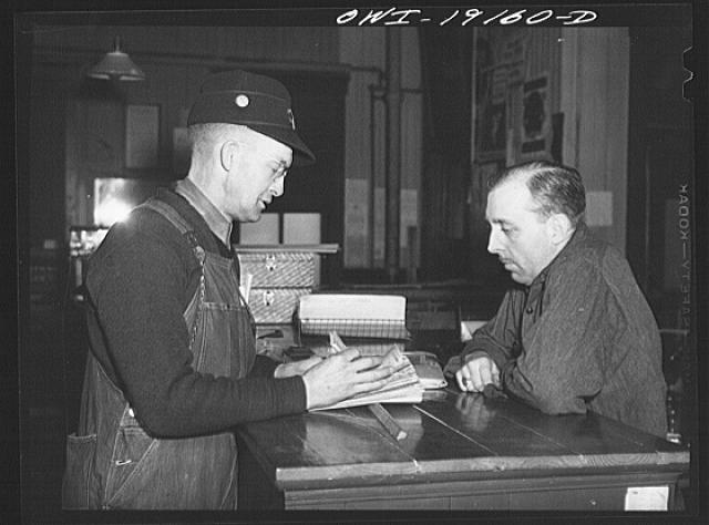 Chicago, Illinois. Atchison, Topeka and Santa Fe Railroad conductor George E. Burton getting his waybills at the Corwith Railroad yard offices