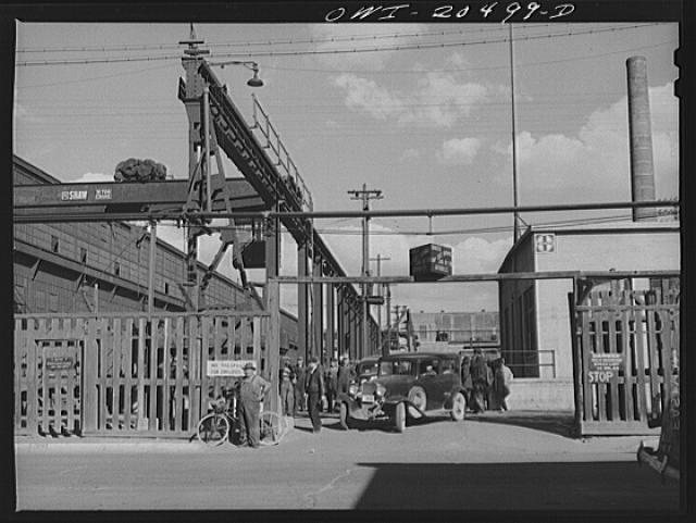 Albuquerque, New Mexico. Workmen coming out of the Atchison, Topeka and Santa Fe Railroad locomotive shops at the end of the day's shift