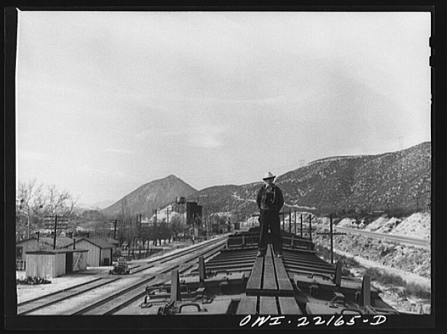 Cajon, California. Swing brakeman riding on top of the Atchison, Topeka, and Santa Fe Railroad train. Brakemen ride the trains in this way during the entire descent from Summit to San Bernardino