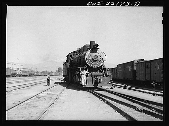 San Bernardino, California. Switch engine and switchman working in the yard used by the Atchison, Topeka, and Santa Fe Railroad