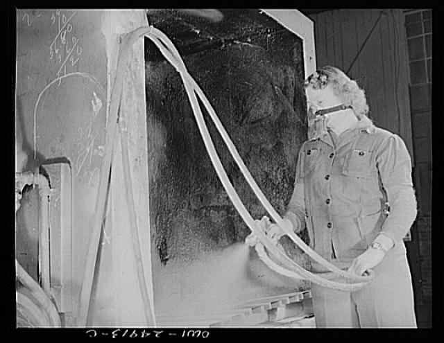Milwaukee, Wisconsin. War production workers at the Heil Company making gasoline trailer tanks for the U.S. Army Air Corps. Elizabeth Little, age thirty, the mother of two children, spraying small parts. Her husband runs a farm