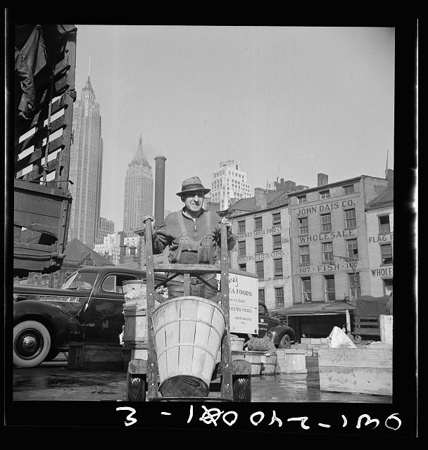 New York, New York. Stevedore who packs and loads crates of fish on the lower east side