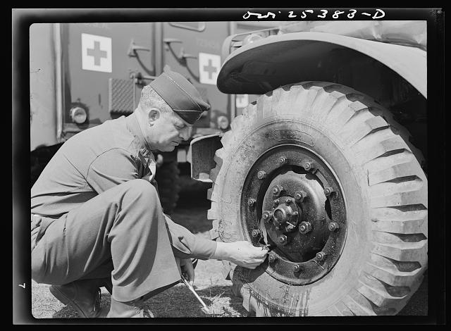 Holabird ordnance depot, Baltimore, Maryland. A careful check is made of air pressure, tire conditions and condition of valves and valve caps before these ambulances are sent overseas
