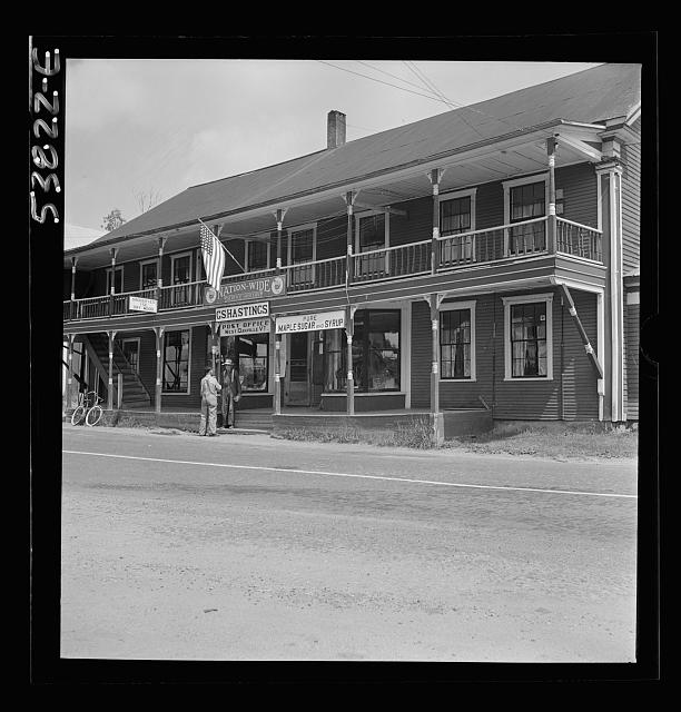 West Danville, Vermont. The two-story porch-framed general store belonging to G. S. Hastings showing the post office sign above the steps and a flag flying over the entrance
