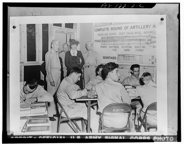 Aberdeen Proving Ground, Maryland. Mrs. Franklin D. Roosevelt looking on as men of the Ordnance Replacement Training Center take an examination in the principles of ammunition supply. Mrs. Roosevelt was particularly interested in observing the methods used by the Army in teaching men who have had little or no formal education. At left is Brigadier General Bethel W. Simpson, who escorted her around the post