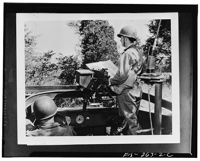 Soldiers of a reconnaissance squad on maneuvers with the Second Army in middle Tennessee cutting across the country in a scout car. Left to right: Corporal Howard Connor, driver; Private Fielder Magruder, radio operator; and Lieutenant Peter Gattino