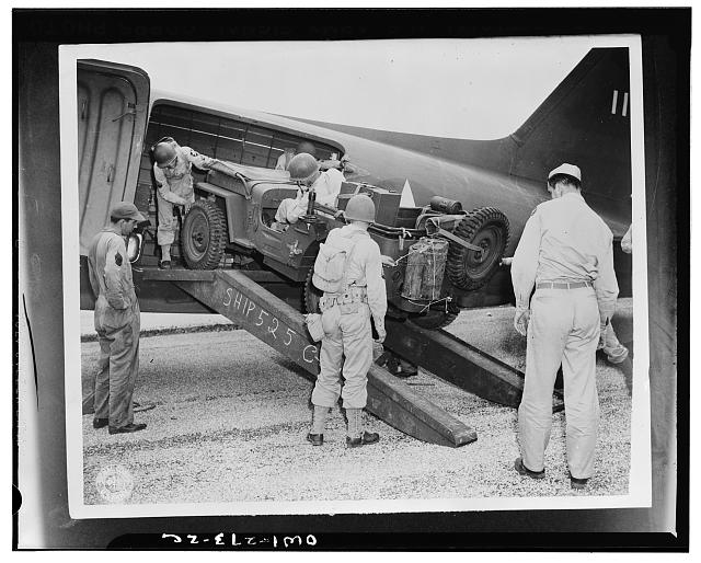 "San Antonio, Texas. From a position behind the ""front lines"", the airborne troopers were rushed to the objective on a split-second schedule to deliver the first blow in a carefully-planned offensive. A jeep is being loaded into a plane as part of this problem"