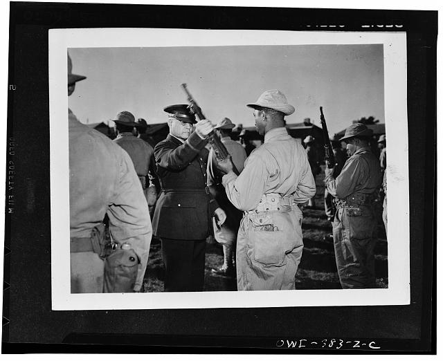 Brigadier General Benjamin O. Davis inspecting the rifle of a U.S. Negro soldier somewhere in England
