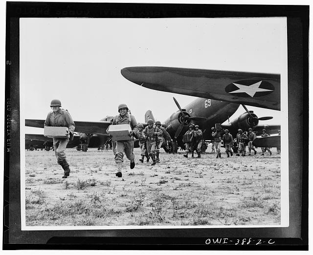 Landing operation of U.S. Airborne Infantry force somewhere in the southwestern United States. Troops unloading supplies and ammunition from transport planes