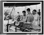 Administering blood plasma to a wounded soldier at the portable hospital in New Guinea. Clayton Mitchell of Wyandotte, Michigan, and Major William Garlick of Baltimore, Maryland, are administering