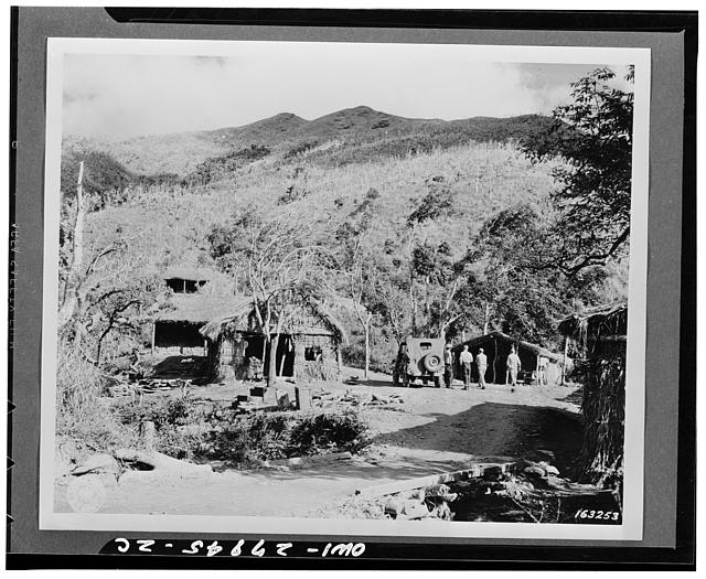 Soldiers live in native-type huts in a small bivouac area of infantry troops somewhere in New Caledonia