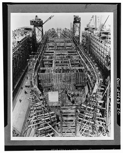 Bethlehem Fairfield shipyards, near Baltimore, Maryland. Construction of a Liberty ship. On the sixth day, 850 tons of the ship are in place. Bulkheads and girders below the second deck are in place. The bulkheads and inner bottom tanks were prefabricated
