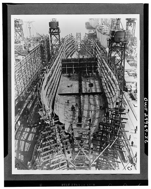 Bethlehem Fairfield shipyards, near Baltimore, Maryland. Construction of a Liberty ship. On the third day the bottom is completed except for forward and aft ends, and on it have been set inner bottom tanks for fuel or ballast. The midships bulkhead has been raised
