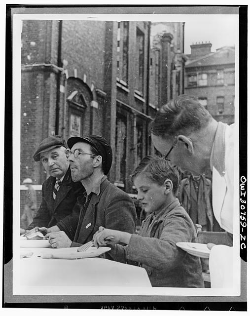 American egg and bacon being enjoyed by workmen and boys at a feeding centre in England