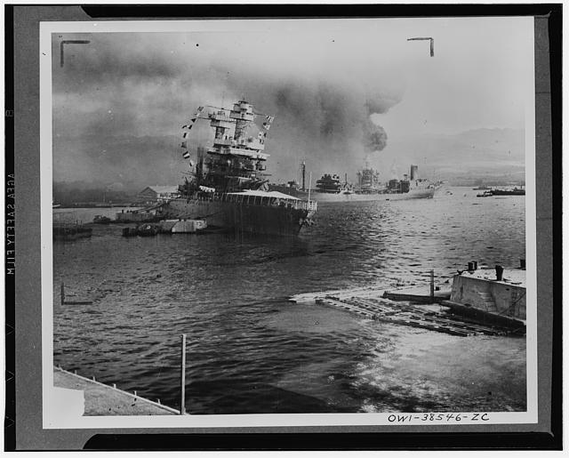 Leaves berth virtually surrounded by stricken ships. The U.S.S. Neosho, navy oil tanker, cautiously backs away from her berth (right center) in a successful effort to escape the Japanese attack on Pearl Harbor, Dec. 7, 1941. At left the battleship U.S.S. California lists after aerial blows. Other crippled warships and part of the hull of the capsized U.S.S. Oklahoma may be seen in the background. The Neosho was later sunk in the Coral Sea