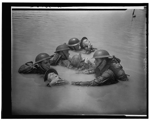 "Soldiers in full field equipment learning the ""chinpull"" method of saving men from drowning"