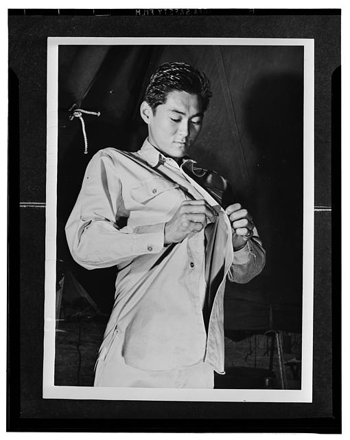 Kauai District, Territory of Hawaii. Mitsuru Doi, first American of Japanese ancestry to volunteer for induction into United States Army, buttoning his uniform shirt