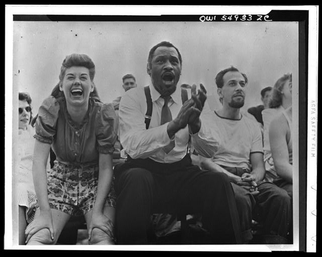 [Paul Robeson and Jose Ferrer watching softball with other members of Othello production, Central Park, New York City]