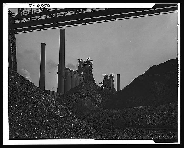 Steel production. The steel industry poised for wartime demands. Huge ore piles await feeding to hungry blast furnaces. Carnegie-Illinois Steel Corporation. Farrell, Pennsylvania
