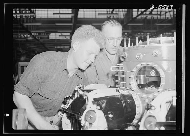 "Production. Aircraft engines. Two of the nation's millions of war workers attach cylinder barrels to one of the ""green"" engines in a huge Midwest aircraft plant. Melrose Park, Buick plant"