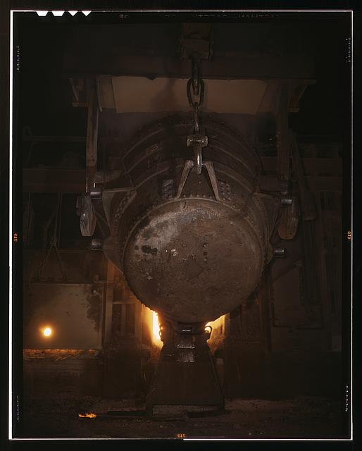 Ladle of molten iron is poured into an open hearth furnace for conversion into steel, Allegheny Ludlum Steel[e] Corp., Brackenridge, Pa. Note the safety latch on the crane hook