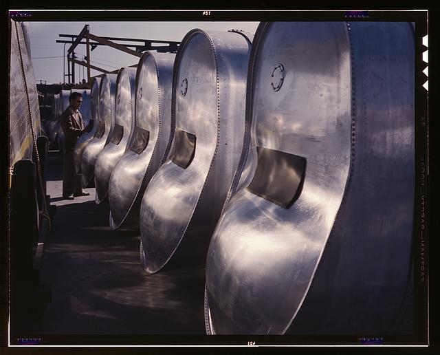"Bomb bay gasoline tanks for long flights of B-25 bombers await assembly in the plant of North American Aviation, Inc., Inglewood, Calif. This plant produces the battle-tested B-25 (""Billy Mitchell"") bomber used in General Doolittle's raid on Tokyo, and the P-51 (""Mustang"") fighter plane which was first brought into prominence by the British raid on Dieppe"