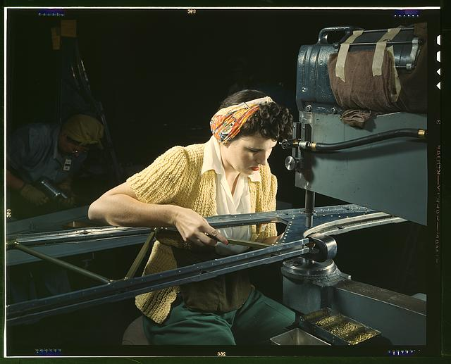 "A girl riveting machine operator at the Douglas Aircraft Company plant joins sections of wing ribs to reinforce the inner wing assemblies of B-17F heavy bombers, Long Beach, Calif. Better known as the ""Flying Fortress,"" the B-17F bomber is a later model of the B-17, which distinguished itself in action in the south Pacific, over Germany and elsewhere. It is a long range, high altitude, heavy bomber, with a crew of seven to nine men -- and with armament sufficient to defend itself on daylight missions"