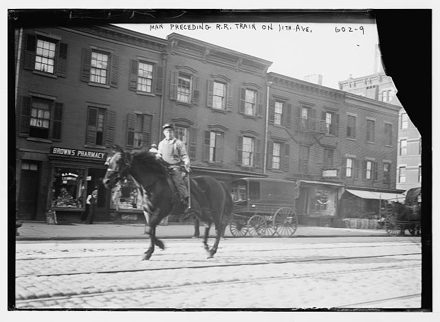 Horseback rider preceding railroad train on 11th Ave., New York City
