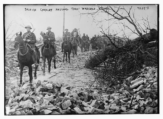 British Cavalry passing through wrecked village