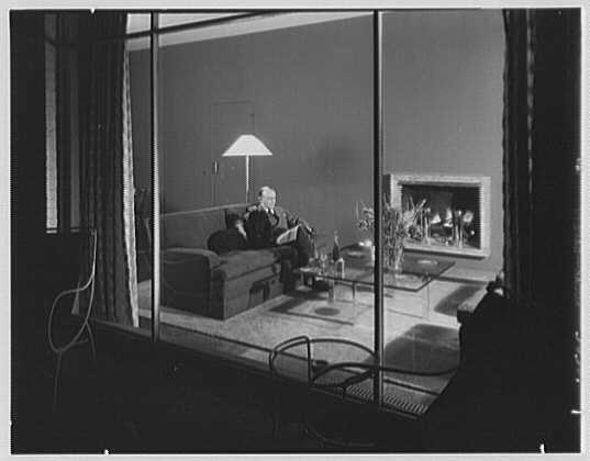 Robert Carson, residence on E. 79th St., New York City. Robert Carson on living room sofa with dog