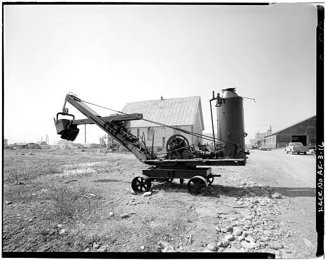 16.  STEAM SHOVEL, LOOKING WEST. ST. JOSEPH'S CATHOLIC CHURCH, NOW USED AS WAREHOUSE, IN BACKGROUND - Hammon Consolidated Gold Fields, Nome, Nome Census Area, AK