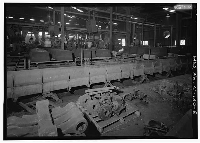 RUN OUTS OCCUR WHEN IRON HAS UNSEATED MOLDING SAND AND RUN OUT OF THE MOLD UNDER POURING JACKETS AND SPILLS ONTO THE MOLDING PLATFORM. WORKERS GENERALLY WAIT SEVERAL MINUTES FOR THE IRON TO SOLIDIFY AND, WHILE IT IS STILL RED-HOT, REMOVE IT FROM THE PLATFORM AND SCRAP THE MOLD. - Southern Ductile Casting Company, Centerville Foundry, 101 Airport Road, Centreville, Bibb County, AL