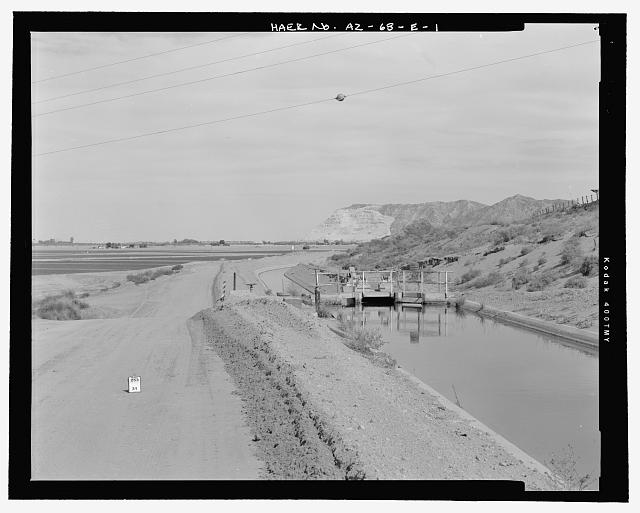 Context view, looking northeast along the Wellton Canal and access road at the Radial Gate Check. Antelope Hill is visible in the background - Wellton-Mohawk Irrigation System, Radial Gate Check with Drop, Wellton Canal 9.9, West of Avenue 34 East & north of County Ninth Street, Wellton, Yuma County, AZ