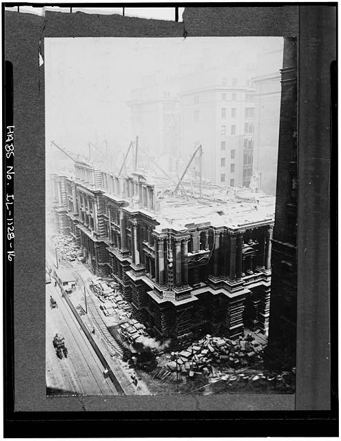 16.  Demolition of sixth city hall,showing crane mounted on railroad ,and upper stories of new county building - Chicago City Hall, 121 North LaSalle Street, Chicago, Cook County, IL