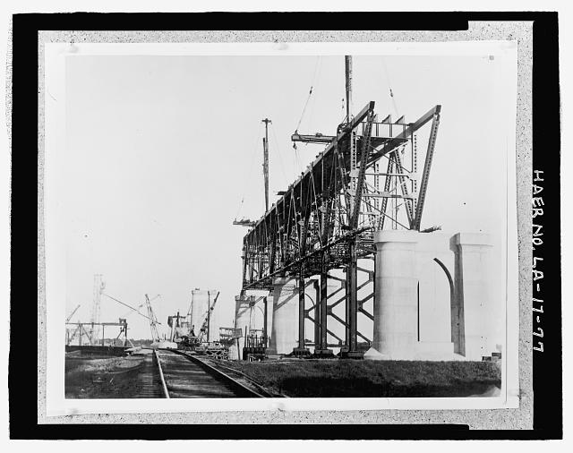 Photographic copy of circa, 1934 black and white photograph.  Loose in oversized box located at the National Museum of American History, Smithsonian Institution, Archives Center, Work and Industry Division, Washington, D.C.  Original Photographer unknown. DECK TRUSS UNDER CONSTRUCTION BETWEEN PIERS C, B, AND V TAKEN AT GROUND LEVEL FROM EAST BANK. - Huey P. Long Bridge, Spanning Mississippi River approximately midway between nine & twelve mile points upstream from & west of New Orleans, Jefferson, Jefferson Parish, LA