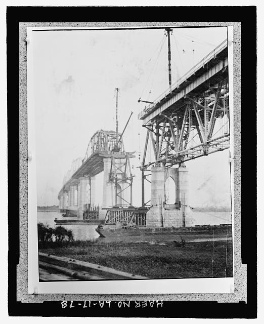 Photographic copy of circa, 1934 black and white photograph.  Loose in oversized box located at the National Museum of American History, Smithsonian Institution, Archives Center, Work and Industry Division, Washington, D.C.  Original Photographer unknown. VIEW FROM EAST BANK LOOKING SOUTH TOWARD WEST BANK AT BRIDGE UNDER CONSTRUCTION SHOWING COMPLETED THROUGH TRUSS SPAN BETWEEN PIER III AND IV AND THE UNCOMPLETED DECK TRUSS SPAN BETWEEN PIER IV AND V. - Huey P. Long Bridge, Spanning Mississippi River approximately midway between nine & twelve mile points upstream from & west of New Orleans, Jefferson, Jefferson Parish, LA