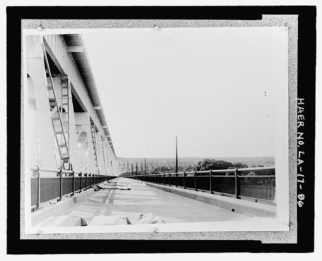 "Photographic copy of 10"" x 14"", black and white photograph mounted on card stock.  Loose in oversized box located at the National Museum of American History, Smithsonian Institution, Archives Center, Work and Industry Division, Washington, D.C.   Original Photographer unknown. PHOTOGRAPH OF WEST BOUND DESCENDING ROADWAY LOOKING SOUTHEAST TOWARD THE WEST BANK.  BRIDGE ROADWAY NEAR COMPLETION, LIGHT POLES IN PLACE, NO FIXTURES. - Huey P. Long Bridge, Spanning Mississippi River approximately midway between nine & twelve mile points upstream from & west of New Orleans, Jefferson, Jefferson Parish, LA"