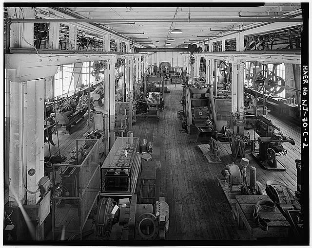 View of shop from platform holding two 40-horsepower electric direct-current motors. These provide power for the shop. Left foreground shows a display of Edison storage batteries which had been shown in the entryway of Building No. 6 by the Edison company during the 1930s through 1950s. - Thomas A. Edison Laboratories, Building No. 5, Main Street & Lakeside Avenue, West Orange, Essex County, NJ