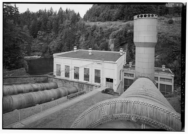 VIEW TO NORTH OF ELWHA RIVER, POWERHOUSE, SURGE TANK, AND PENSTOCK.  PHOTO BY JET LOWE, HAER, 1995. - Elwha River Hydroelectric System, Elwha Hydroelectric Dam & Plant, Port Angeles, Clallam County, WA