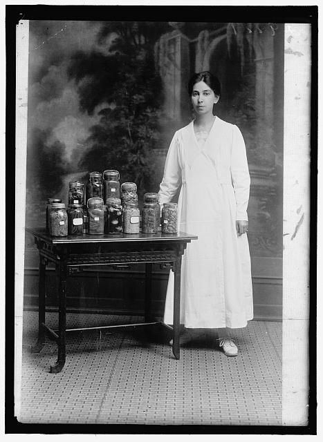 [Woman standing next to table holding a display of preserved food in glass jars, including peas, beans, fruit, and eggs]