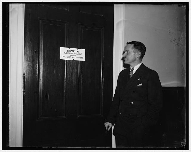 Lobbyists taboo at Capitol. Washington, D.C., Jan. 8. Rep. Alfred M. Phillips Dem. of Stanford, Conn. looks over the sign that hangs on his office door, saying that as yet no lobbyists has passed his portals. He would recognize a lobbyist by his talk the Congressman states