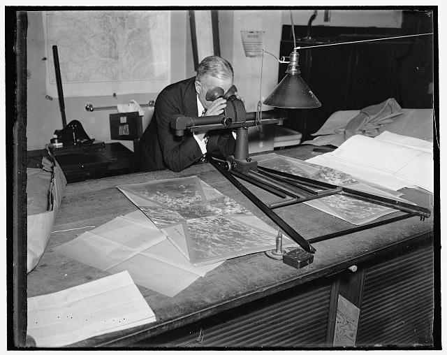 Geological Survey. Washington, D.C., March 13. Albert Pike using a stereoscope on a pair of photographs to bring out the relief and locate objects for a map