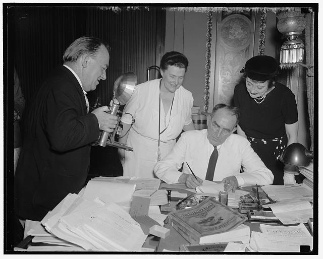 "Speaker signs last minute bills. Washington D.C., Aug 21. Rep. John J. O'Connor New York, Chairman of the House Rules Committee, ""shoots"" Speaker Bankhead as he signs the last minute bills passed by the House before their adjournment tonight. Others in the picture are Rep. Mary T. [Norton] (left) of New Jersey; and Mrs. Bankhead, 8/21/37"