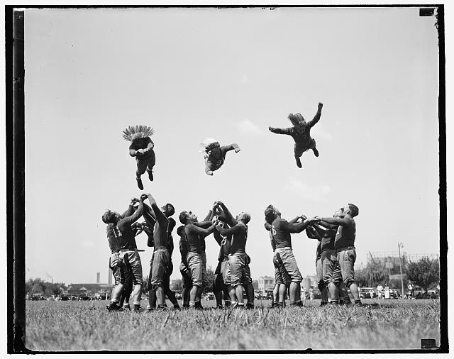 "Washington Redskins start training. Washington, D.C. Aug. 28. He-man exercise took the place of calisthenics today as the Redskins, Washington's entry in National Professional Football League, started training. The boys ""flying thru the air"" are, left to right: Millner (Notre Dame), Rentner (Northwestern) and Peterson (West Virginia) Wesleyan) 8/28/37"