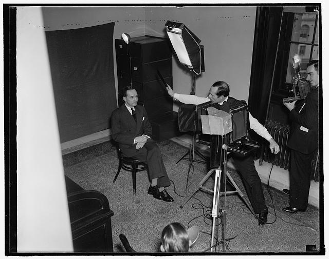 Watches birdie. Washington, D.C., Jan. 7. Edsel Ford, auto magnate, poses for the Harris-Ewing photographer just before he is questioned by the Senate Rail Investigating Committee today, 1/7/38