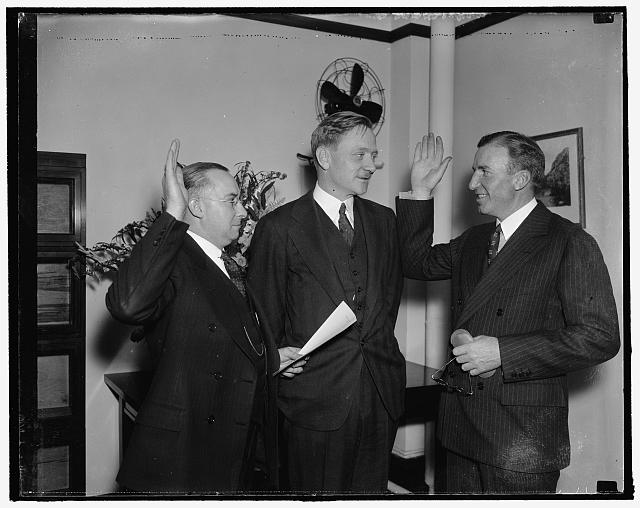 Former Wall Street broker sworn in as member of Security and Exchange Commission. Washington, D.C., Jan. 13. J.W. Hanes, being sworn in as member of the SEC. Hanes is being sworn in by Frank P. Brassor, Secretary to the Commission while William O. Douglas, Chairman of the Commission, center, looks on, 1/13/38