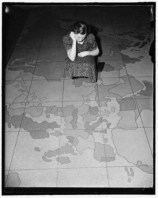 European situation spoils map on Post Office department floor. Washington, D.C., April 12. The huge map on the floor of the Post Office Department here is all out of kilter these days due to the aggression in Europe. Many are the embarrassing questions being asked officials about when Mr. Farley is going to do something about Ethiopia, Austria and Czechoslovakia. The answer so far has been - nothing. Probably the Post Office is waiting to see what will happen next on the continent. Miss Edna Strain is inspecting the damage done by the ambitious dictators. 4-12-39