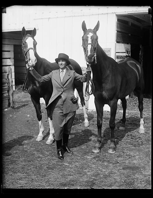 Wife of New York department store magnate captures first and second prizes at Washington Horse Show. Mrs. Bernard Gimbel, wife of the New York department store magnate, and her horses Capt. Doane (left) and welcome with with whom she captured first and second prizes in the Ladies Hunters class at the National Capital Horse Show today. Capt. Doane is the $12,000 dollar horse who has been capturing many blue ribbons in eastern horse shows recently